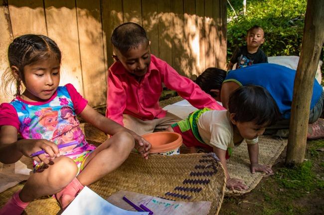ninos-jugando haciendo dibujo sobre un petate
